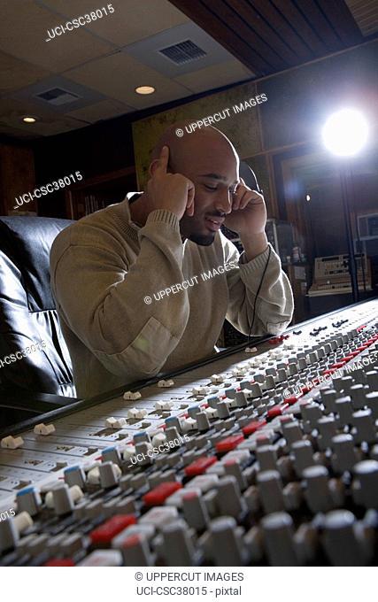 Music producer listening to headphones
