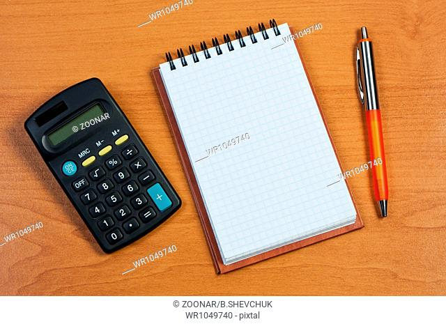 Calculator, notepad and pen on wooden background