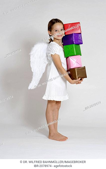 Girl dressed up as a Christmas angel with gifts, Christmas