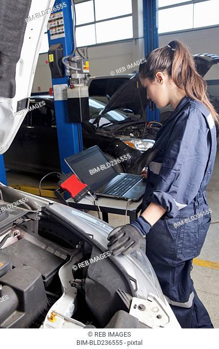 Hispanic mechanic diagnosing car engine with laptop