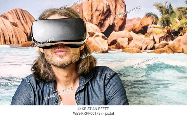 Portrait of man wearing Virtual Reality Glasses in front of photographic wallpaper