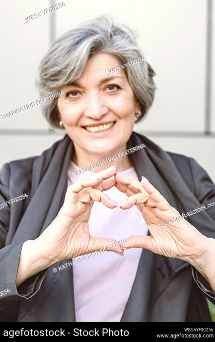 Smiling businesswoman making heart with finger while standing against wall