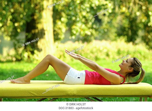 Young blond woman doing sit-ups on a mat in the park