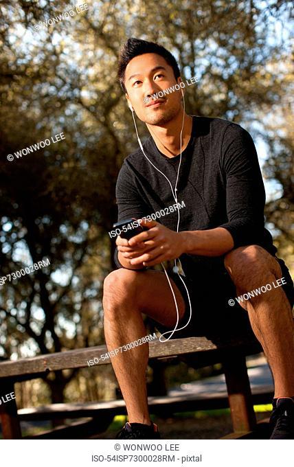 Man listening to earphones outdoors