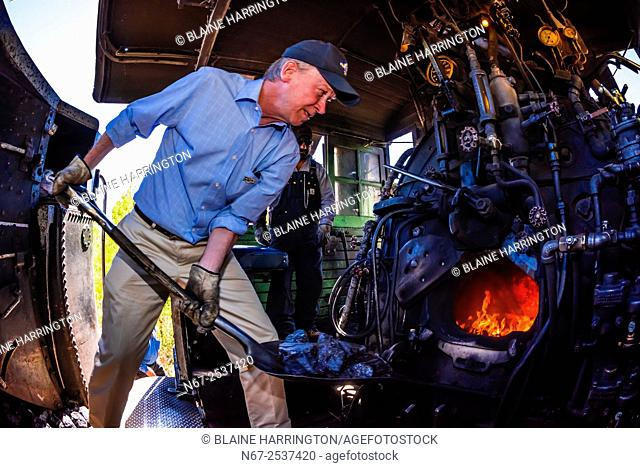 Governor John Hickenlooper (of Colorado) acts as the train fireman adding coal, stoking the boiler on the steam locomotive on a visit aboard the the Cumbres &...