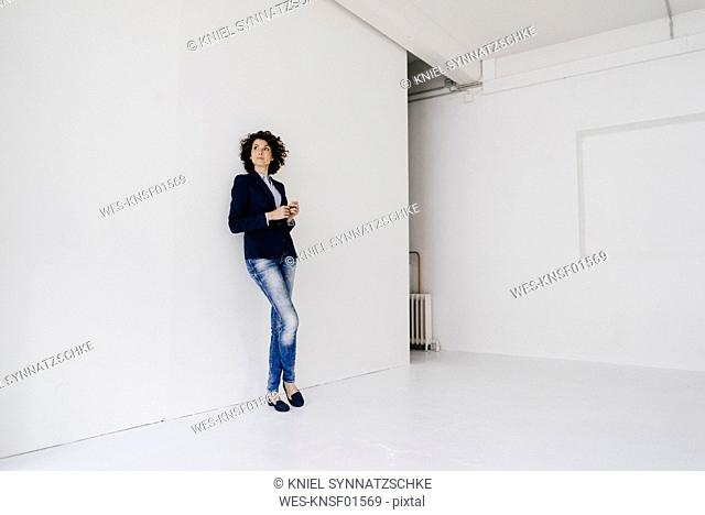 Businesswoman standing in loft , leaning against wall