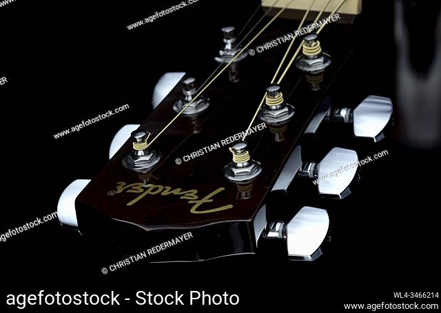 Close up image form a classic guitar on a black background painted with light
