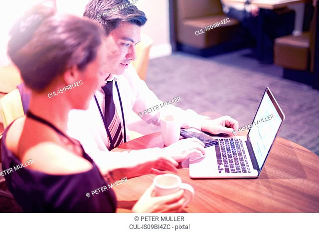 Businessman and woman sitting in airport lounge, using laptop