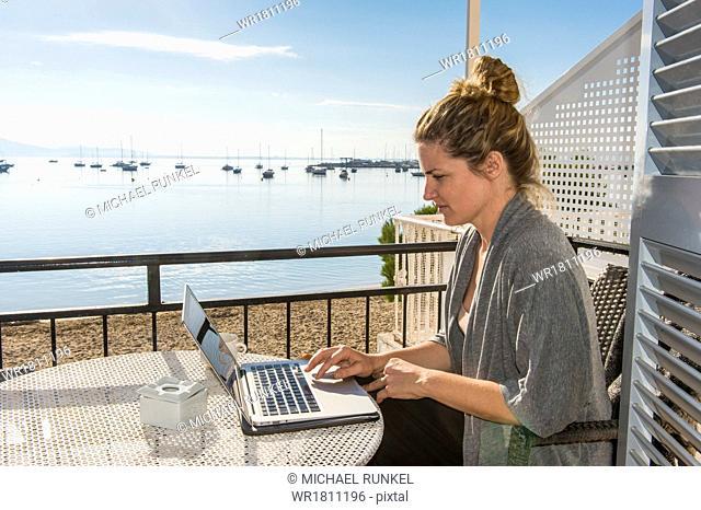 Woman working on her laptop on a balcony overlooking the ocean, Port de Pollenca, Mallorca, Balearic Islands, Spain, Mediterranean, Europe