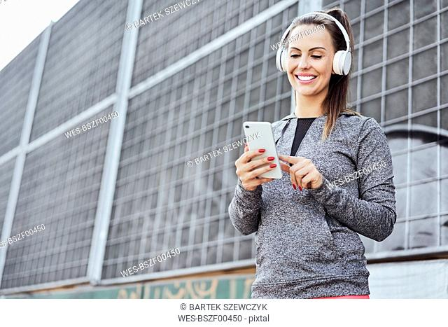 Woman with headphones using smartphone