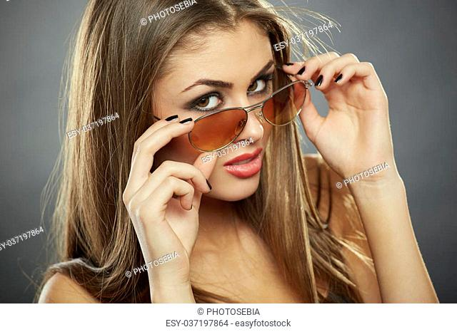 Flirtatious woman holding and looking over sunglasses with seductive eyes on grey background