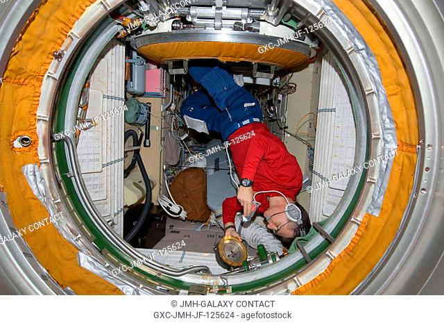 While wearing a communication system headset, European Space Agency astronaut Paolo Nespoli, Expedition 26 flight engineer