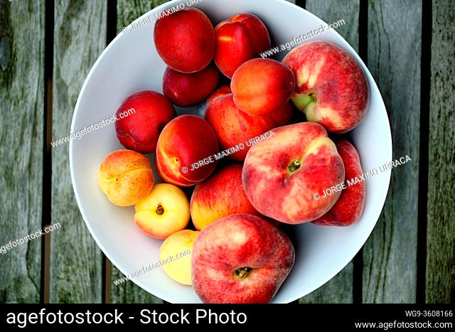 Summer fruits in white bowl on wooden table view from above