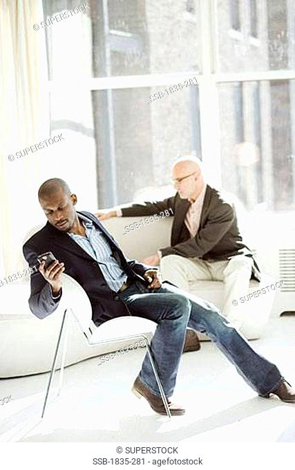 Businessman sitting on a chair and holding a mobile phone with another businessman using a laptop behind him