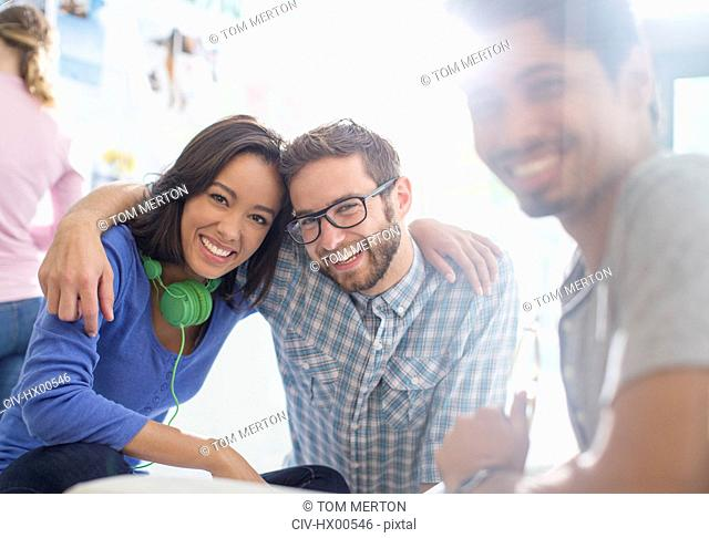 Portrait creative business people with headphones hugging in sunny office