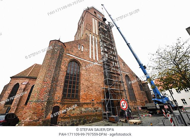 Bell technicians transport a 1.7 ton heavy bronze bell into the tower of the St. Petri church with the help of a crane in Wolgast, Germany, 09 November 2017