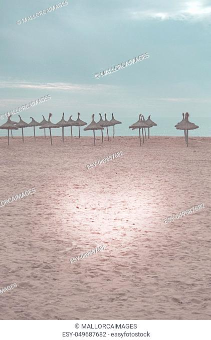 Beautiful sand beach with light heart and straw parasols toned in color Living Coral