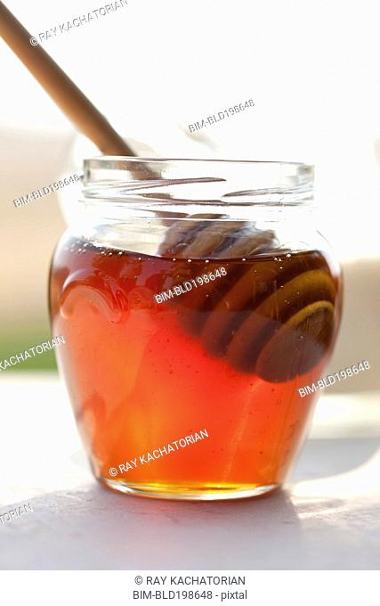 Close up of honey and wooden dipper