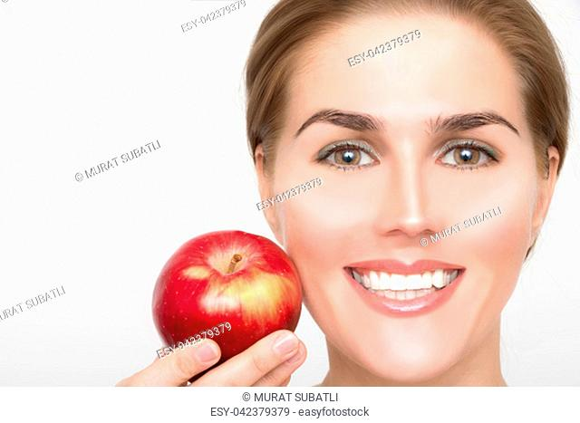 Face of a beautiful blonde woman with a red apple in her hand