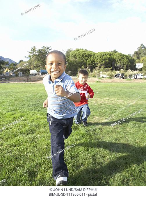 Two boys running through field