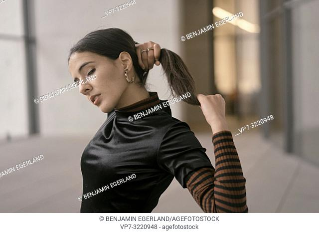 portrait of sensitive fashionable woman with closed eyes, indoors, making pigtail, pensive thoughtful feelings, in Munich, Germany