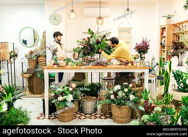 Florists arranging flower while standing at flower shop