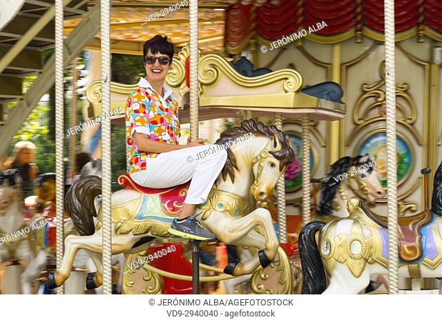Woman riding traditional gallopers on a carousel ride, Santander. Cantabria Spain, Europe