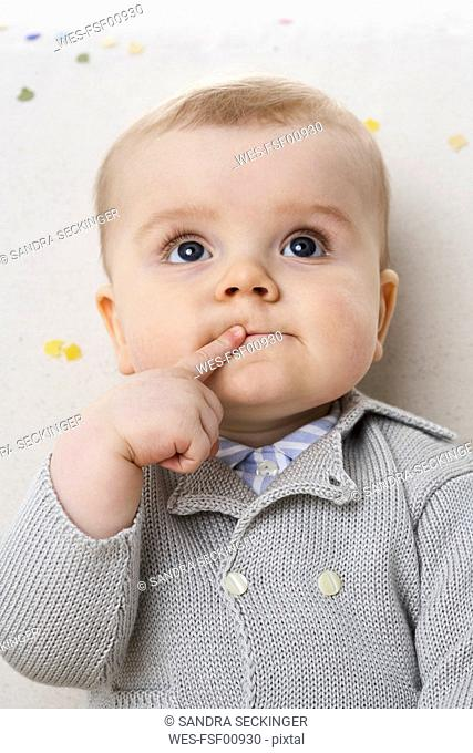 Portrait of pensive baby boy with finger on his mouth