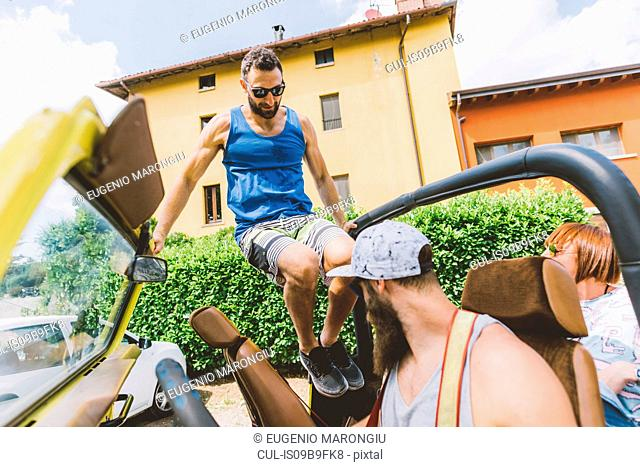 Young man on road trip jumping into off road vehicle, Como, Lombardy, Italy