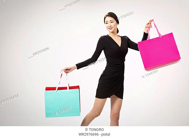 Young smiling woman in black dress posing with shopping bags