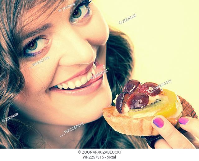 Closeup funny woman eating fruit cake