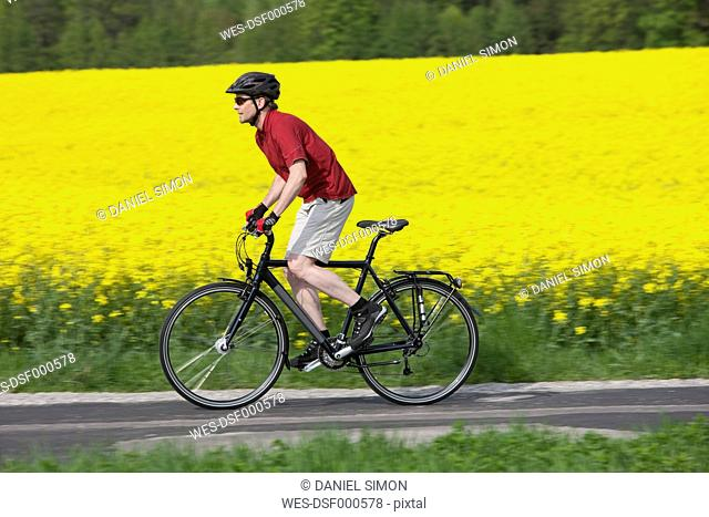 Germany, Bavaria, Starnberg, Mature man cycling through country road