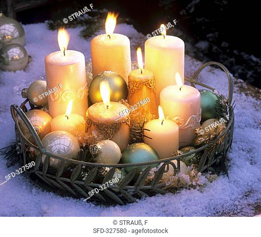Candles and Christmas baubles on tray in snow evening
