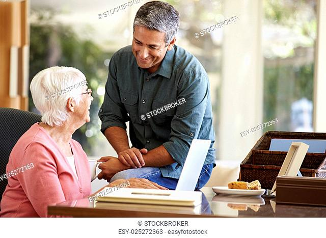 Adult Son Helping Mother With Laptop