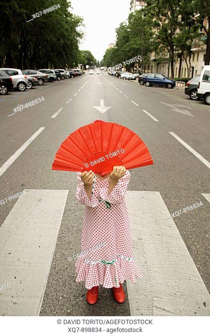 Girl on the street holding fan