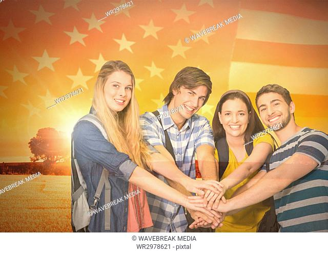 Friends with hands together agaisnt american flag and beautiful landscape