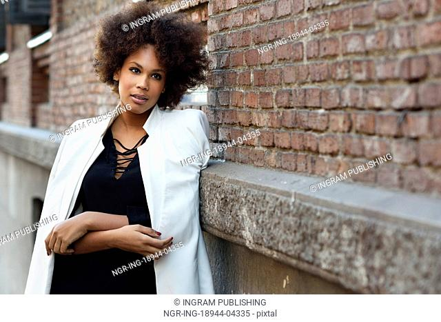 Young black woman with afro hairstyle standing in urban background. Mixed girl wearing white jacket and black dress posing near a brick wall
