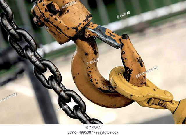Steel chain and large yellow old industrial hook