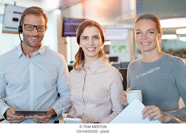 Portrait smiling, confident business people with digital tablet and coffee in office