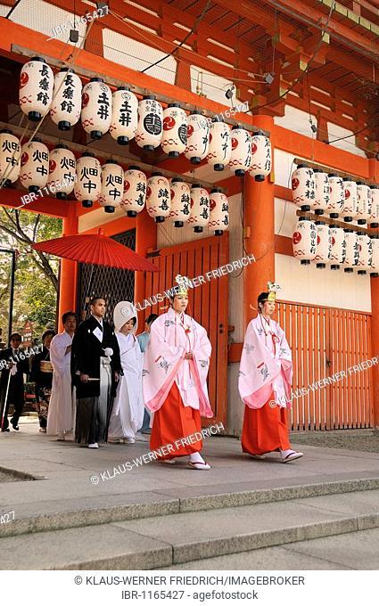 Entry of the bridal procession at a Shinto wedding, walking through the shrine gate, entering the shrine, led by mikos, Yasaka Shrine, Maruyama Park, Kyoto