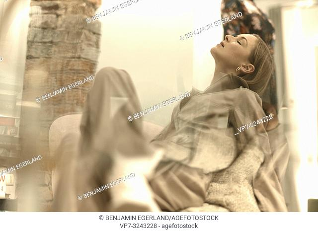 desire for fashion, fashionable woman resting in armchair, closed eyes, passion, in Munich, Germany