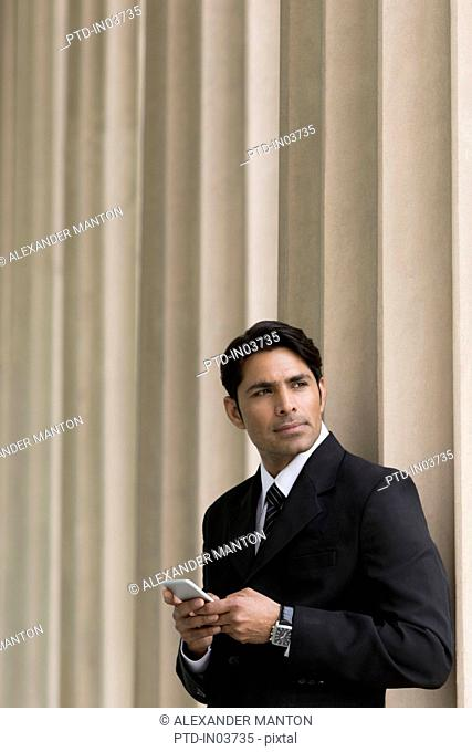Businessman looking up from mobile phone