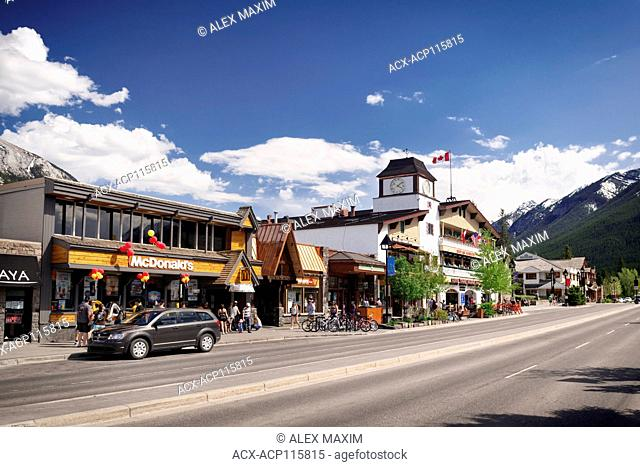 Street scenery of McDonald's and other shops and restaurants on Banff Avenue, downtown of Banff in Alberta Rockies with Rocky Mountains in the background