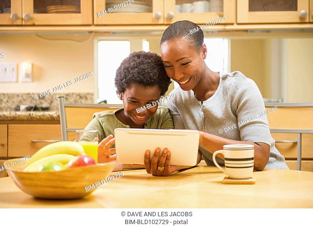 African American mother and daughter using digital tablet in kitchen