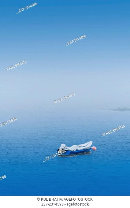 A covered boat moored in a calm sea in foggy conditions, Halifax, Canada