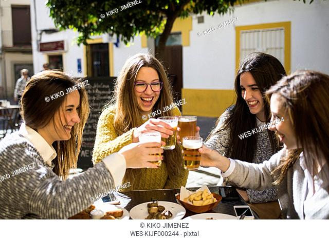 Four happy friends toasting with beer in a street cafe