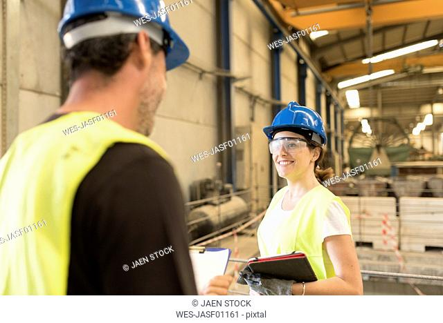 Two smiling colleagues in factory hall