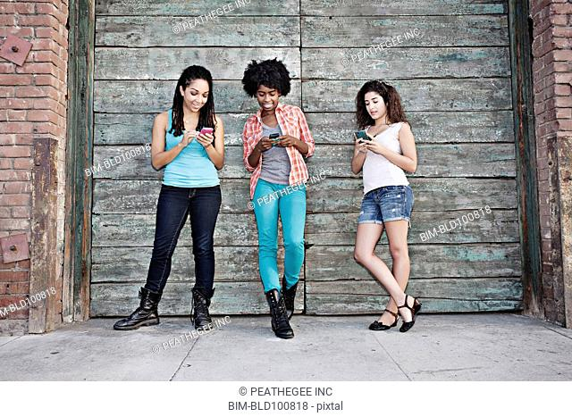 Women text messaging on cell phones