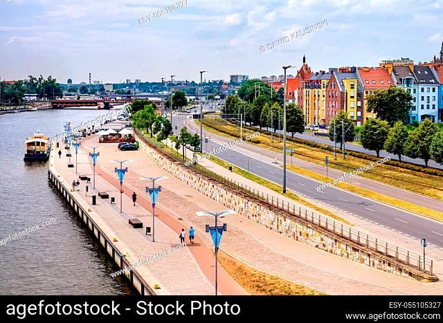 Piastowski Boulevard on Odra River embankment with ships converted to restaurants. People walking and relaxing on river bank in old town quey