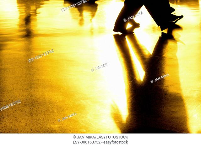 Abstract creative photo of people silhouettes of walking people and their shadows on golden background
